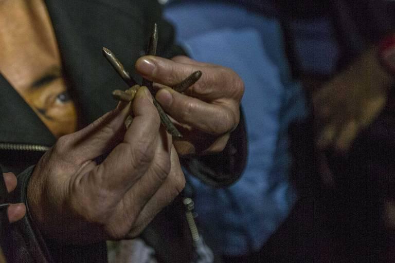 Homem mostra ganchos de metal pontiagudos lançados na estrada por opositores do ex-presidente Lula e que furaram um pneu de um dos ônibus da comitiva