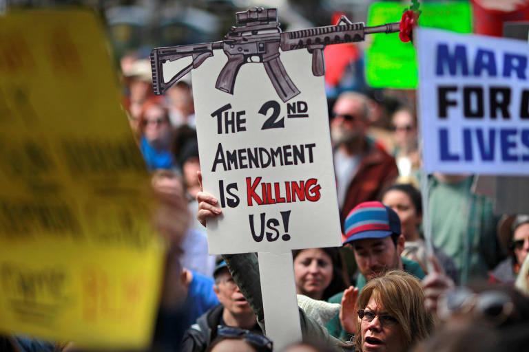 Manifestante aparece entre multidão entre outros cartazes segurando cartaz com um fuzil desenhado na parte superior e a mensagem abaixo