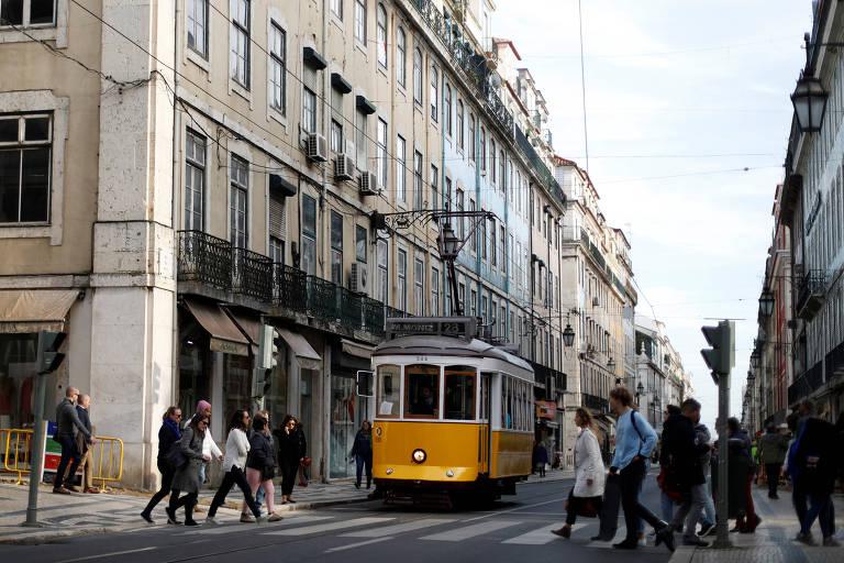 Bonde amarelo prossegue em trilho perto de faixa de pedestres, em que pessoas esperam para atravessar em rua do centro histórico de Lisboa