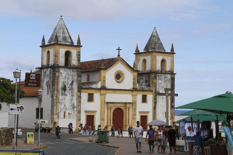 Igreja branca e amarela, antiga, em praça