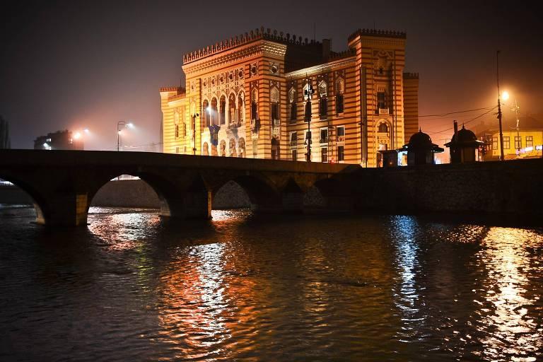 Cena noturna: uma ponte sobre um rio com um prédio iluminado ao fundo