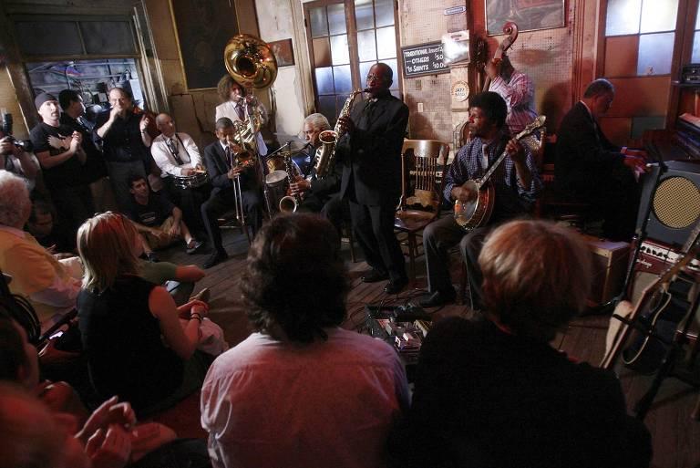 Homens tocam instrumentos de jazz enquanto público assiste