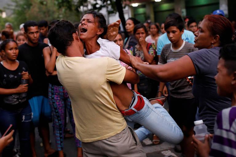 Homem segura nos braços mulher que grita de desespero; ao lado, outras pessoas tentam apartá-la