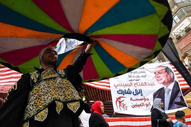 Dervixe (místico islâmico) levanta tecido colorido enquanto dança ao lado de cartaz do presidente  do Egito, Abdel Fattah al-Sisi, perto de uma seção eleitoral; ao fundo passam duas mulheres com véu islâmico