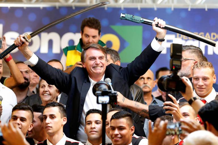 O presidenciável Jair Bolsonaro ergue uma espada durante passagem em Curitiba