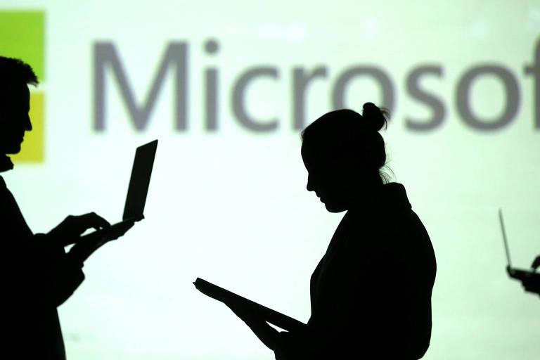 Silhuetas de pessoas segurando laptops em frente à logomarca da Microsoft
