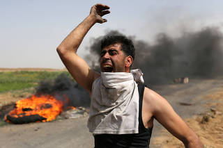 A Palestinian shouts during clashes along the Israel border with Gaza ahead of a protest in a tent city, demanding to return to their homeland, in the southern Gaza Strip