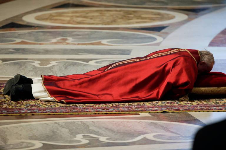 No Vaticano, Papa Francisco ora deitado no chão, com rosto apoiado em uma almofada vermelha durante missa da Semana Santa nesta sexta-feira (13)