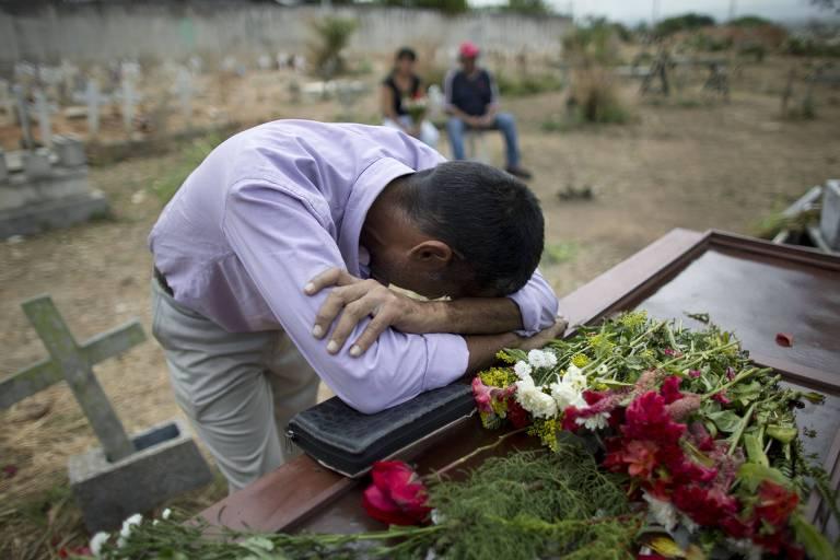 Jesus Zapata chora sobre o caixão com os restos mortais de seu filho, Erickson Zapata, 23, uma das 68 vítimas do incêndio na carceragem de Valencia