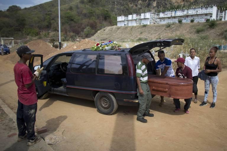 Parentes retiram caixão no cemitério de Valencia, onde três túmulos coletivos foram abertos para receber 32 das 68 vítimas do incêndio em cadeia