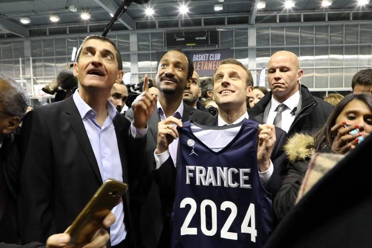 """Grupo de pessoas olha pra cima enquanto uma delas segura uma camiseta onde está escrito """"France 2024"""""""