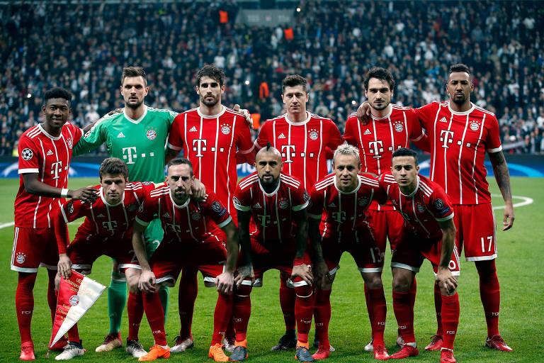 Onze homens com uniforme vermelho posam para foto em gramado