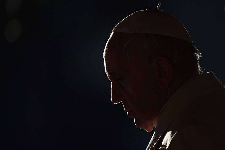 Papa Francisco aparece com o rosto em silhueta olhando para baixo durante cerimônia da Via-Crúcis