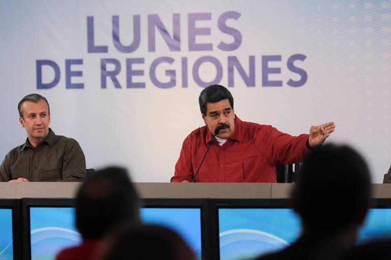 """De camisa vermelha, Nicolás Maduro aparece falando em um microfone de mesa, com Tareck el-Aissami à sua esquerda, de camisa marrom; ambos estão sentados a uma mesa e são observados por outras pessoas do outro lado, que formam uma plateia e aparecem de costas; ao fundo dos dois, aparece no painel a inscrição """"Lunes de Regiones"""" (segundas-feiras de regiões, em espanhol)"""