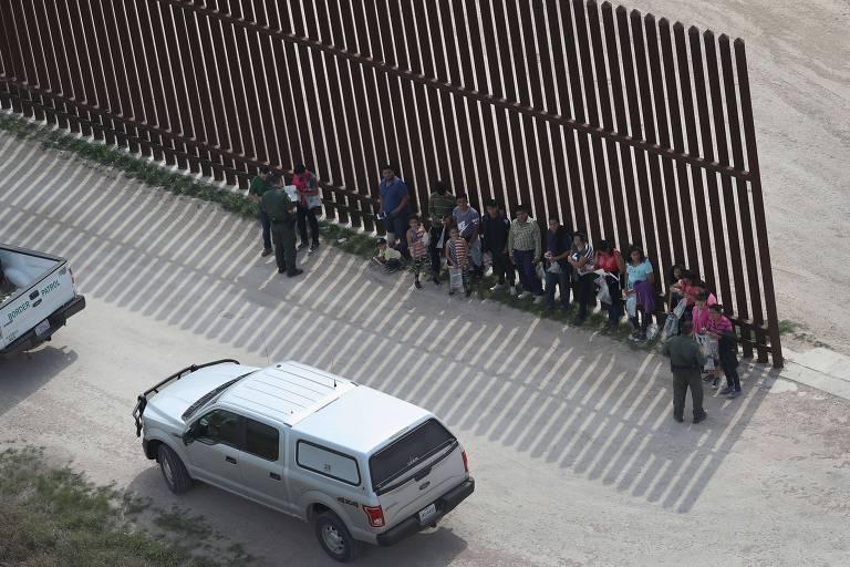 Agentes da patrulha de fronteira abordam grupo de imigrantes na cerca entre EUA e México perto de McAllen, Texas