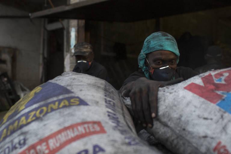 O venezuelano Luis Willians, 27, que trabalha empacotando de carvão em um comércio no Bairro Santo Antônio, em Manaus, segura sacos