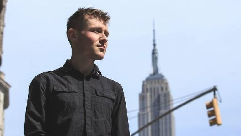 Patrik Hermansson aparece em uma foto em uma rua; ao fundo aparece um arranha-céu e um semáforo