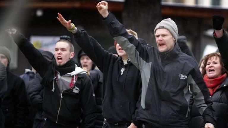 Três homens brancos vestidos de preto fazem a saudação nazista em um protesto de grupos de extrema-direita