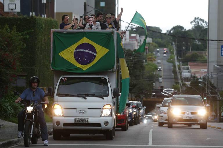 Caminhão com bandeira do Brasil e adereços em verde e amarelo seguido por vários carros