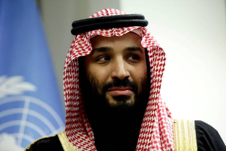 O príncipe saudita Mohammed bin Salman aparece sério em entrevista; ao fundo do lado esquerdo, uma bandeira da ONU