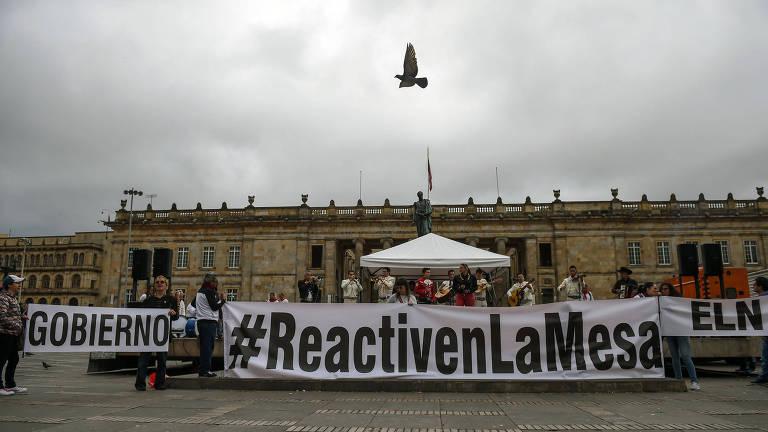 """Manifestantes seguram faixas, em espanhol, com as expressões em espanhol """"governo"""", """"reativem a mesa"""" e """"eln"""" em frente a um dos prédios da praça Bolívar, em Bogotá; uma pomba aparece voando acima do grupo no céu nublado"""