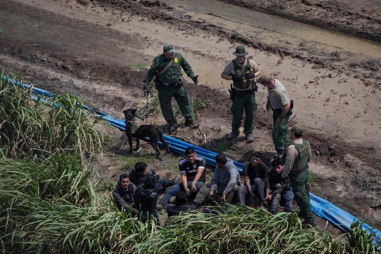 De farda verde, membros da patrulha de fronteira ficam de pé ao lado de um grupo de cinco imigrantes ilegais, sentados no chão ao lado de um matagal, que é dividido com uma lona azul de uma estrada de terra onde estão os agentes