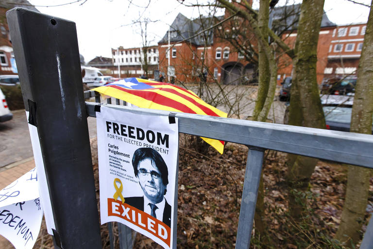 Manifestantes colocaram cartazes em defesa de Puigdemont em frente ao prédio onde o ex-presidente catalão está detido na Alemanha