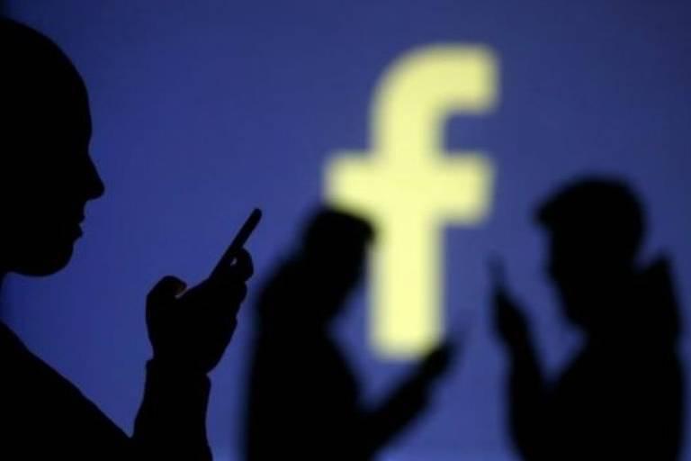 Usuários de celular á frente do logotipo do Facebook