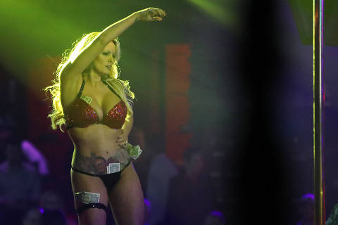 (FILES) In this file photo taken on March 9, 2018 the actress Stephanie Clifford, who uses the stage name Stormy Daniels, performs at the Solid Gold Fort Lauderdale strip club in Pompano Beach, Florida. 