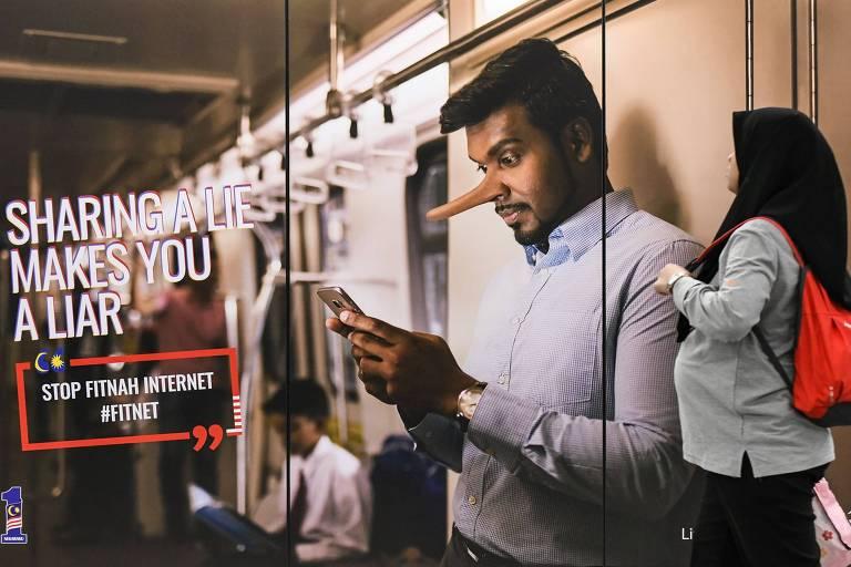 Propaganda contra a disseminação de notícias falsas em estação de trem na Malásia