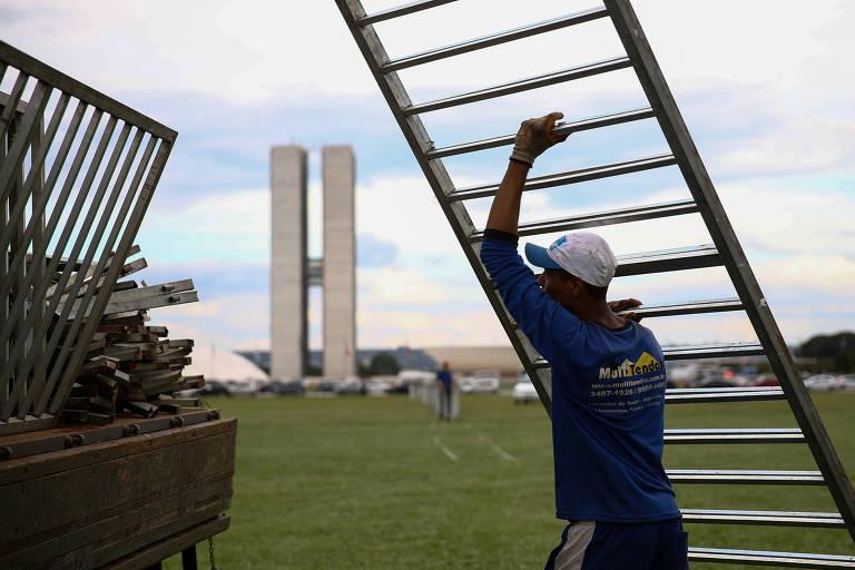 Homem monta grades de segurança no gramado do Congresso Nacional