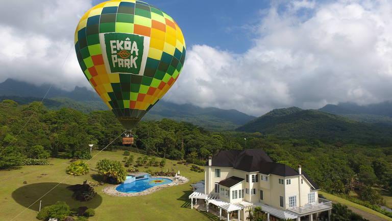 Balão colorido voa ao lado de casa bege, em gramado