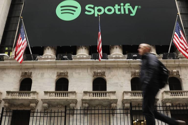 Pessoa caminha em frente a Bolsa de Nova York (Nyse), quando Spotify inicia comércio de ações