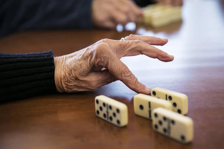 mãos de mulher segurando peças de dominó