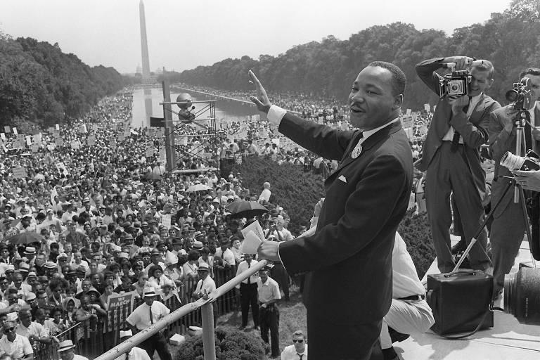 Martin Luther King Jr. levanta a mão de cima de um palco ao acenar a seus seguidores, que ocupam o National Mall, em Washington