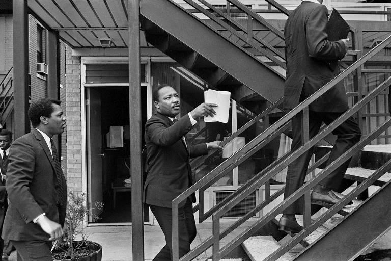 Martin Luther King Jr. carrega papéis nas mãos enquanto sobe primeiro degrau da escadaria que leva ao segundo andar do hotel Lorraine; assessores o acompanham: um à frente e outro atrás