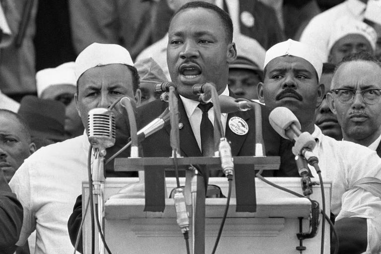 Martin Luther King aparece atrás por cinco microfones, enquanto seguidores o observam do palco do evento