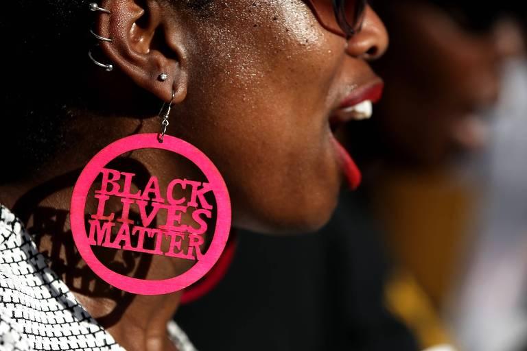 """Mulher negra aparece de boca aberta com brinco redondo rosa na orelha com a expressão """"Black Lives Matter""""; rosto dela aparece até a altura do nariz"""