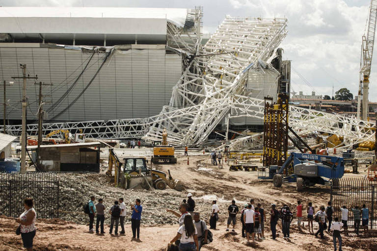 Operários e curiosos observam o acidente nas obras da Arena Corinthians, em São Paulo, onde parte da cobertura desabou causando mortes de dois operários em 27 de novembro de 2013.