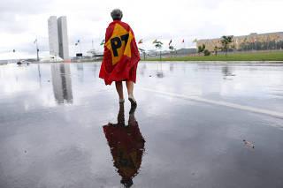 A supporter of former Brazilian President Luiz Inacio Lula da Silva walks on Esplanade of Ministries before of the supreme court issues a new verdict in Lula corruption case, in Brasilia