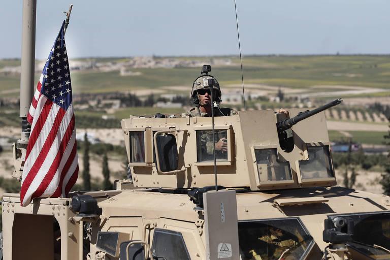 Com capacete, soldado americano aparece ao alto de um veículo blindado, controlando arma longa; à esquerda do militar, aparece uma bandeira americana pendurada; ao fundo, campo aberto verde