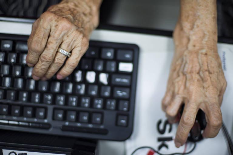 Mãos de idosos manuseiam um mouse e um teclado