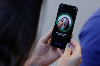 A woman sets up her facial recognition as she looks at her Apple iPhone X at an Apple store in New York