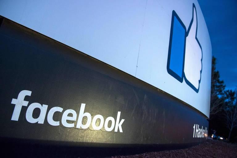 Placa mostra o logo do Facebook em preto, com um endereço ao lado; acima, o símbolo de curtir sob fundo azul claro