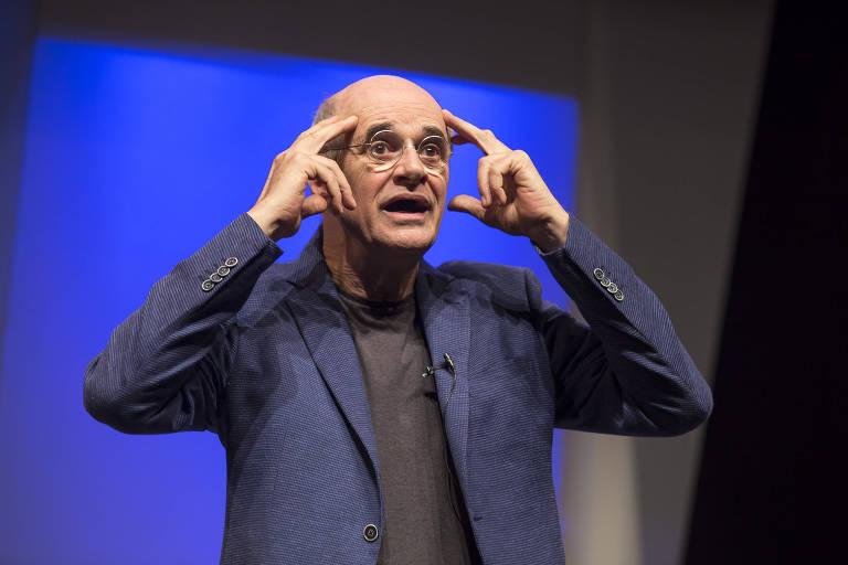 """O ator Marcos Caruso em cena do monólogo """"O Escândalo Philippe Dussaert""""; ele veste blazer azul e calça marrom e óculos; o palco é iluminado com amplos fachos de luz"""