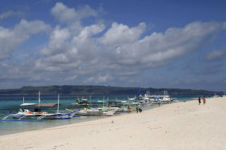 FILE PHOTO: Traditional boats line up the shore in a secluded beach on the island of Boracay, central Philippines