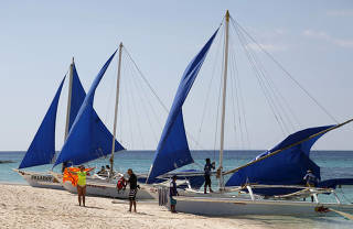 FILE PHOTO: Tourists takes photographs along local sailboats on the island of Boracay, central Philippines