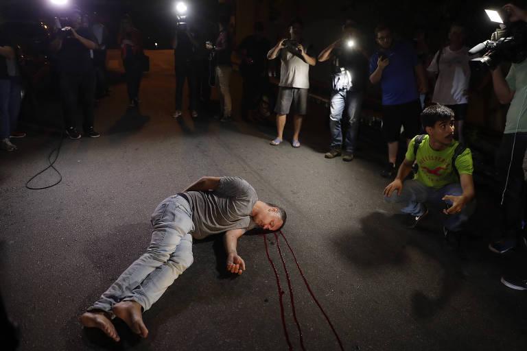 Homem deitado no chão e sangrando