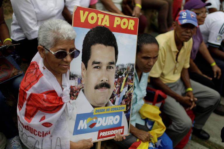 Com bandeira branca e vermelha, mulher de óculos escuros segura cartaz; a seu lado direito, dois homens: um carrega uma bandeira venezuelana no colo e o outro usa um boné com as cores de Cuba