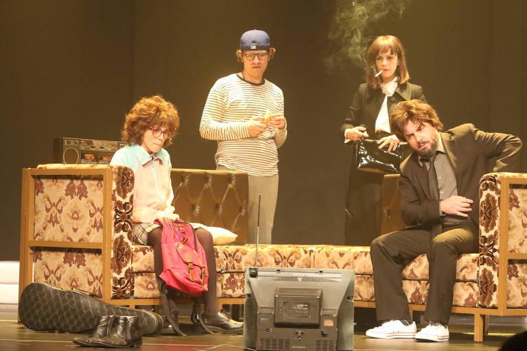 A atriz Débora Falabella está sentada em um sofá, ao lado de três atores, em cena da peça